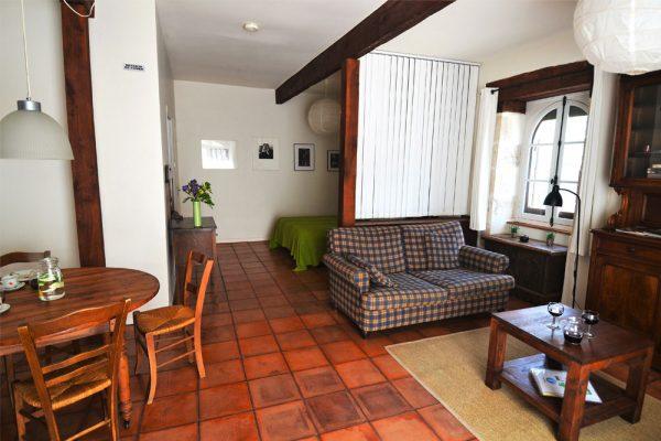 Slaapruimte, zithoek en eethoek van de gastenkamer Manseng