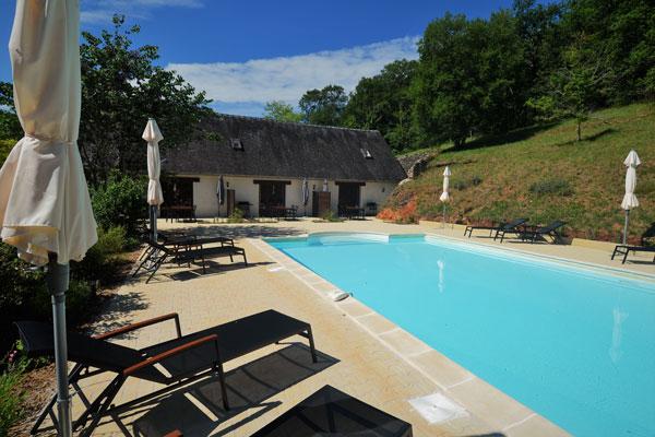 zwembad en ligzetels op Le Manoir in Souillac